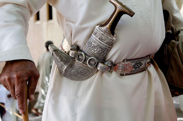 Omani man wearing a Khanjar or Jambiya, the traditional engraved silver knife, Nizwa Souk, Oman