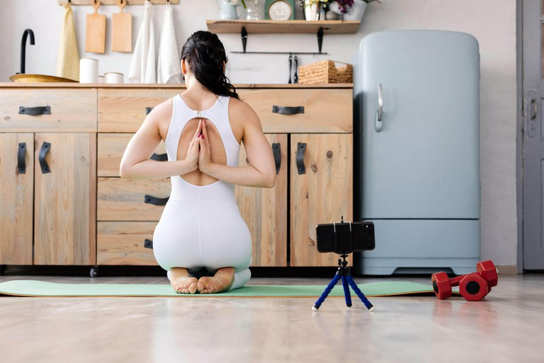 Young girl doing yoga fitness exercise at home