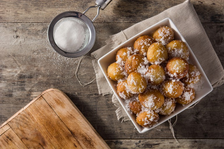 Carnival fritters or bunuelos de viento for holy week on wooden table. Top view. Copy space