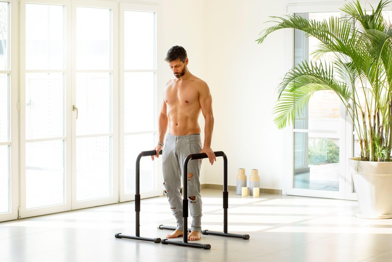 Fit muscular athlete ready to perform calisthenics exercises on parallel bars as the man stands psyching himself up for his workout in a high key gym