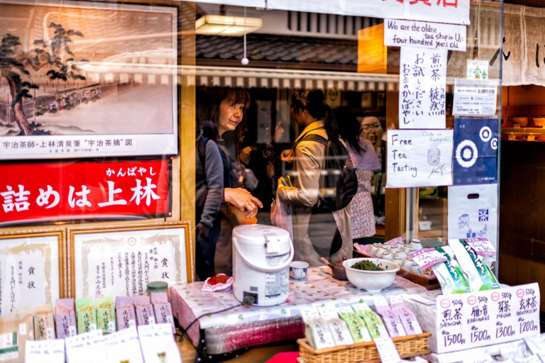 Uji, Japan - April 14, 2019: Traditional village with oldest store shop selling green tea free tasting sample with sign in english