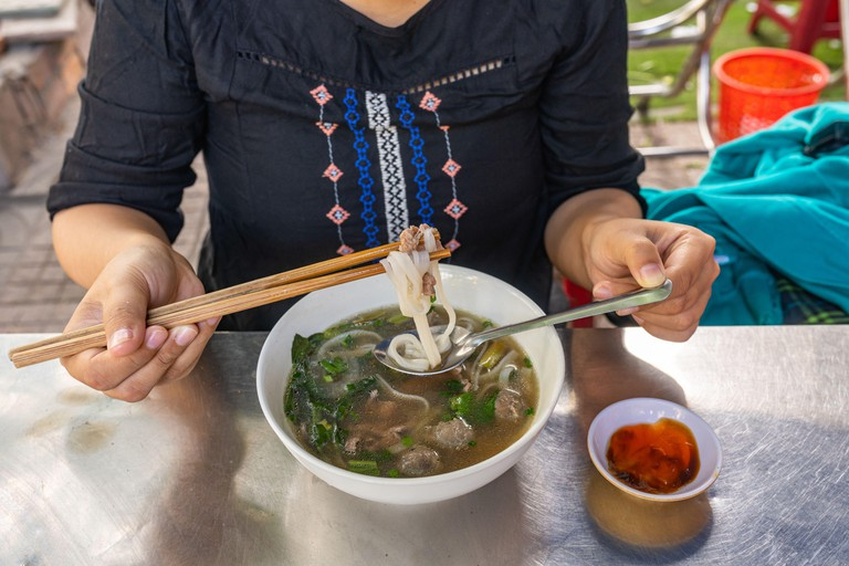 Woman eating beef Pho noodle soup