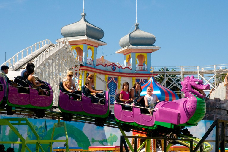Riding the Silly Serpent at Luna Park, St Kilda, Melbourne, Australia. Behind is the century-old Scenic Railway rollercoaster