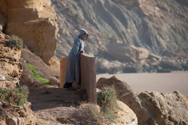 Local Moroccan man in kaftan looking out to sea from the cliff side, Imsouane, Morocco
