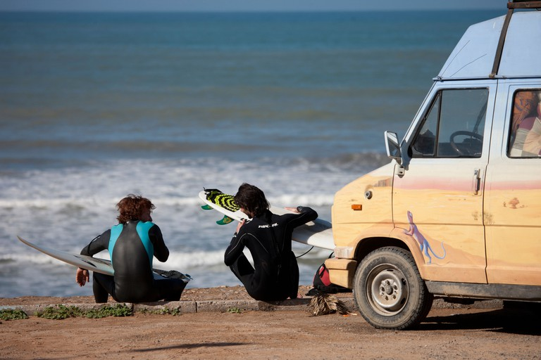 Surfers and surfboards sitting chatting by the van and the sea.