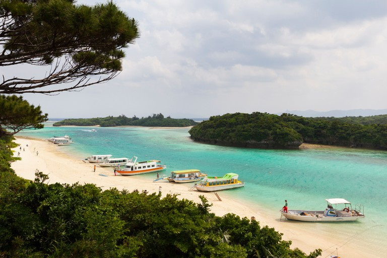 Boats line the sandy beach at Kabira Bay, Ishigaki Island, Okinawa