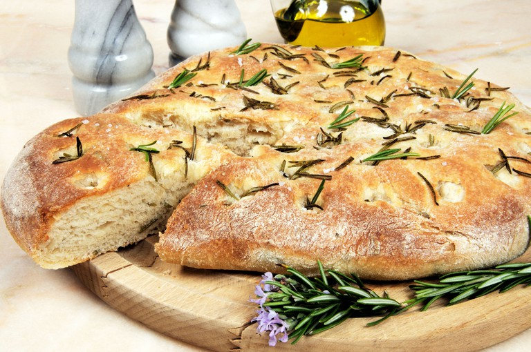 Italian rosemary Focaccia bread on a marble table top.