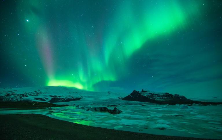 the Northern Lights (Aurora Borealis) over the Vatnajokull galcier and Fjallsarlon, eastern Iceland