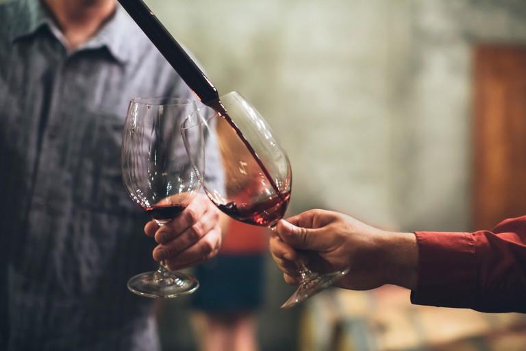Caucasian men tasting wine in cellar