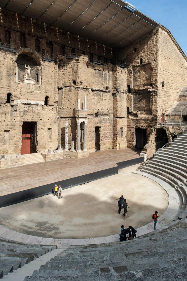 Tourists in auditorium and scaenae frons of the Roman Theatre antique d'Orange / Ancient Theater of Orange, Vaucluse, France