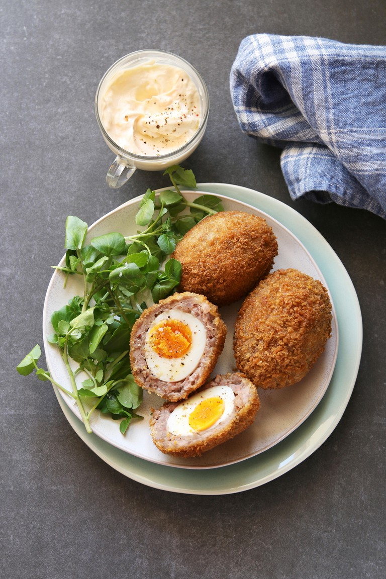 Scotch eggs on a plate with watercress salad and mayonnaise dip