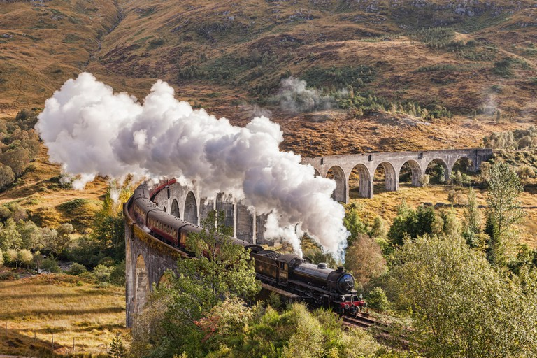 The Jacobite steam train blows steam from the exhaust as it crosses the Glenfinnan Viaduct, Highland, Scotland, UK.
