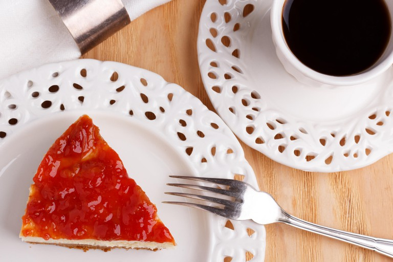Cheesecake with goiabada jam, white vintage cup of coffee. Selective focus