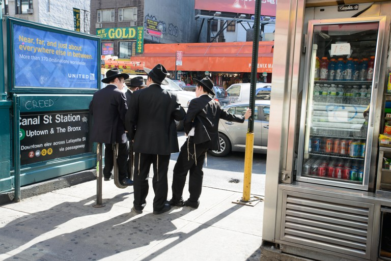 Hasidic/Orthodox Jewish men next to a subway station on Canal Street in New York's Lower East Side