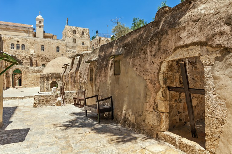 Wooden cross and stone monastic cells on the roof of the Church of the Holy Sepulchre in Jerusalem, Israel.