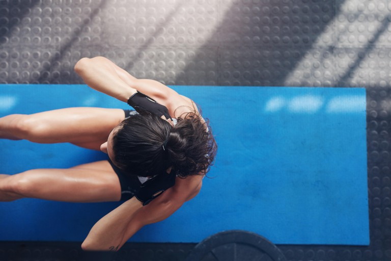 Overhead view of female working out at the gym. Muscular young woman doing sit ups on an exercise mat.