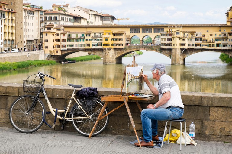 An artist on the Ponte Santa Trinita in Florence, Italy, working on a painting