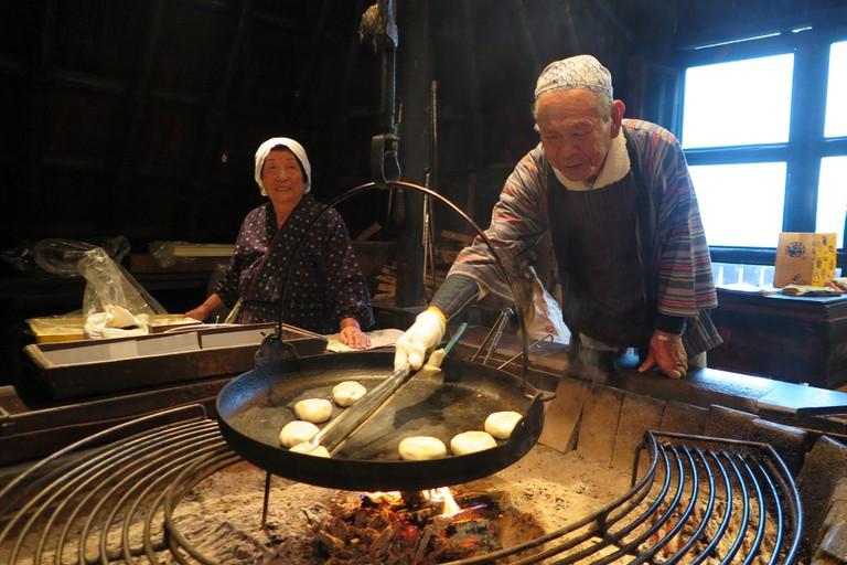 Okayki bakers Chikayoshi Gonda and his colleague Matsumoto prepare traditional oyaki, a round Japanese dumpling, over a fireplace in Nagano, Japan.
