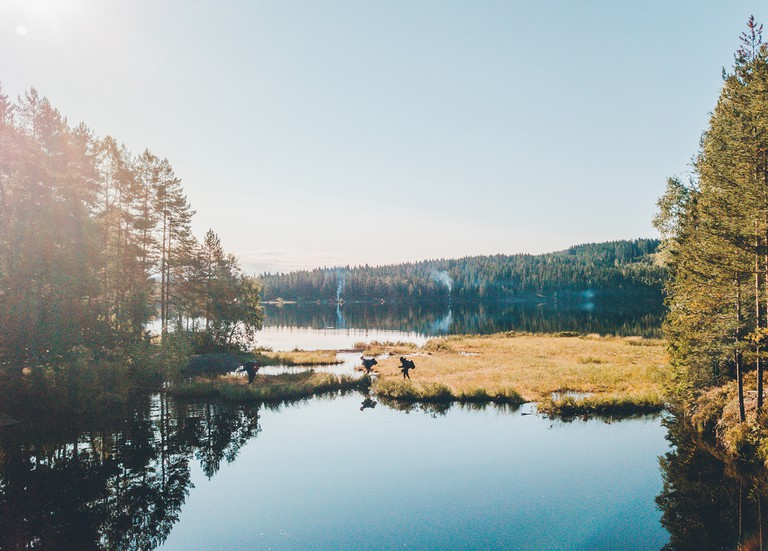 People hiking over dam in the forest of Oslo, Norway.
