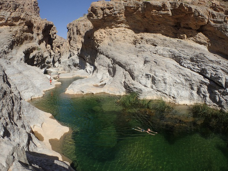 OMAN, wadi bani khalid, a group of european tourists swim in the green water of a canyon