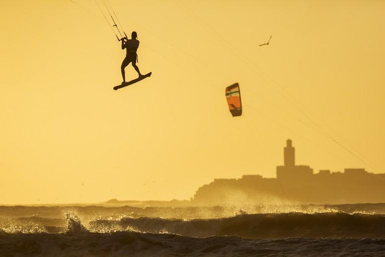 Kitesurfers enjoying big waves at sunset in Essaouira