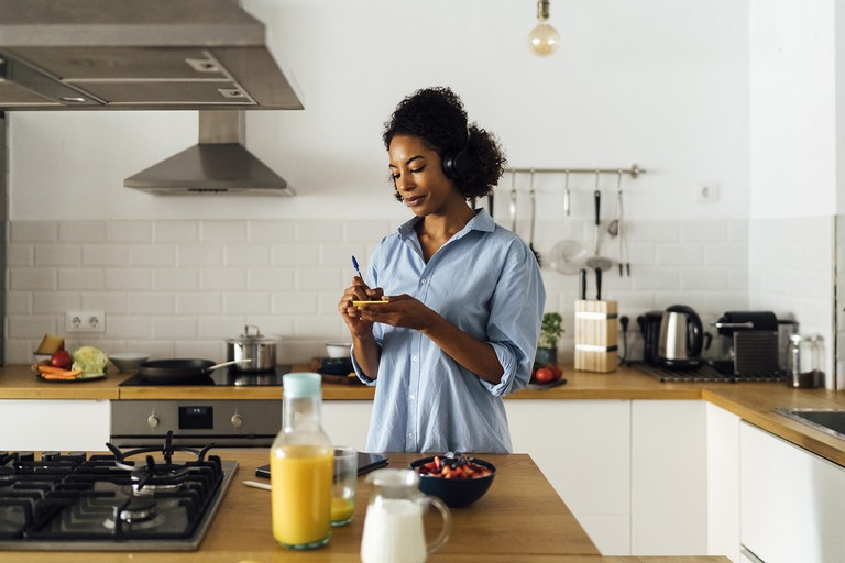 Woman in her kitchen in the morning, writing notes