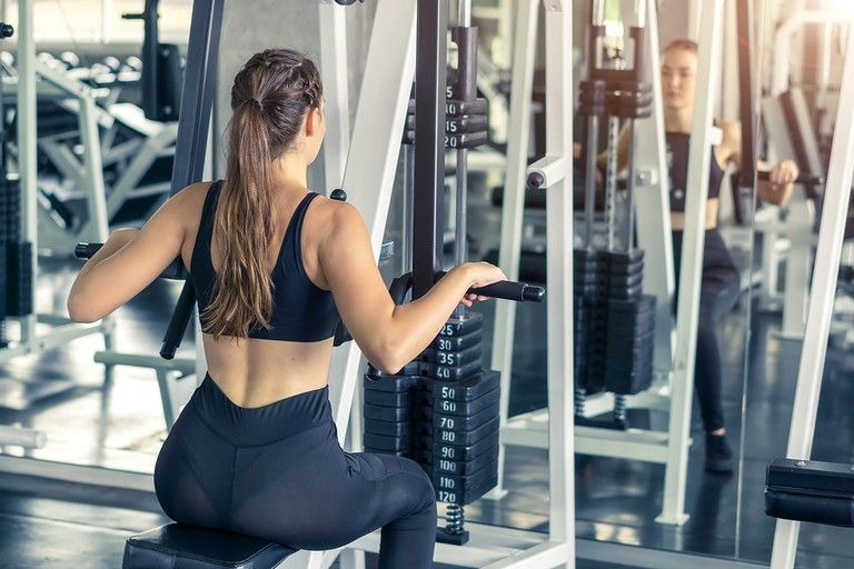 Fitness, sport, training and lifestyle concept - Young women flexing muscles  in fitness gym center