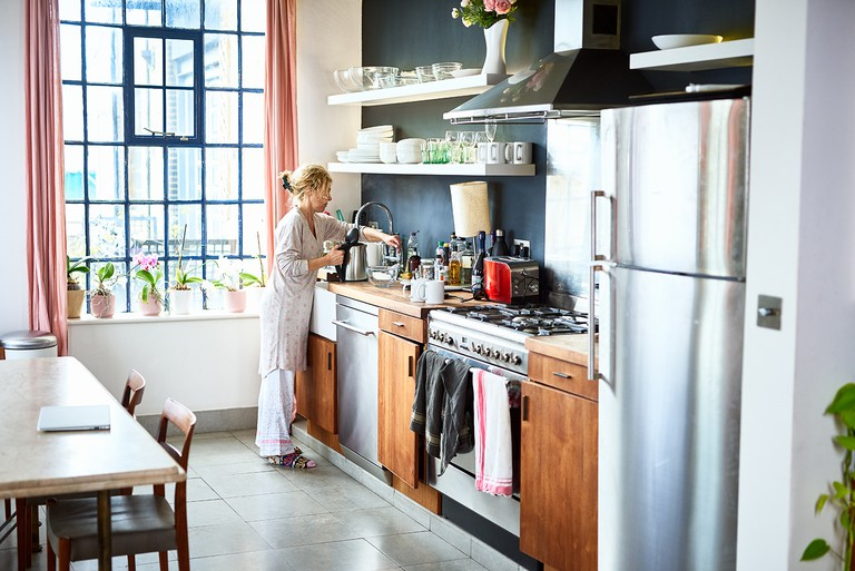 Mature woman filling kettle at kitchen sink