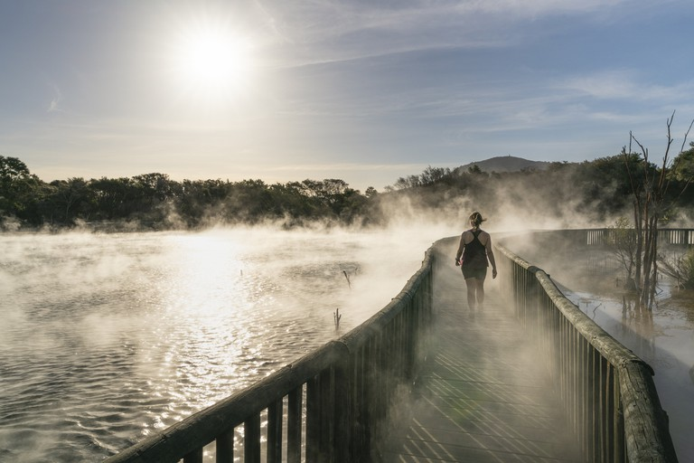 Woman walking on a footpath at Kuirau Park, Rotorua, NZ.
