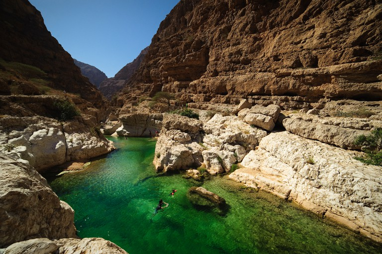 Two people swimming in the turqoise waters of Wadi Shab, Oman