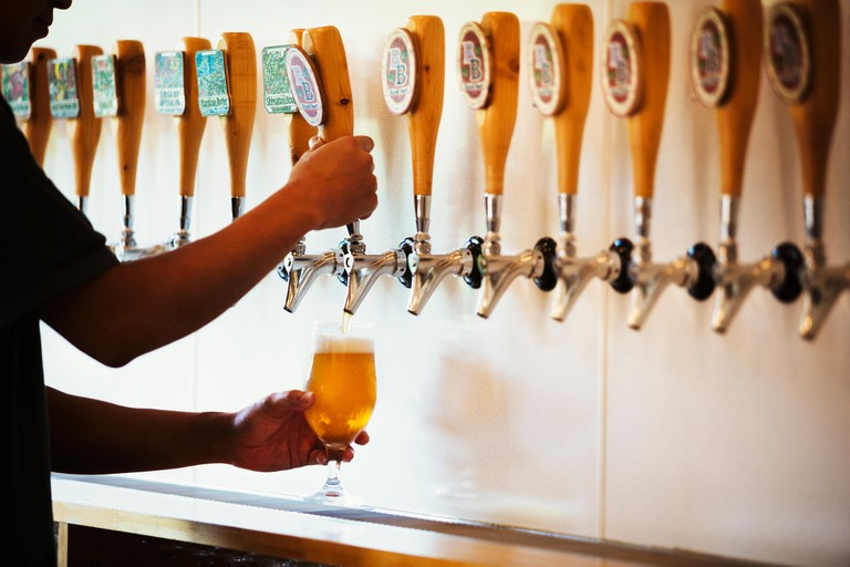 Man pulling a glass of craft beer from a tasting bar in a brewery.