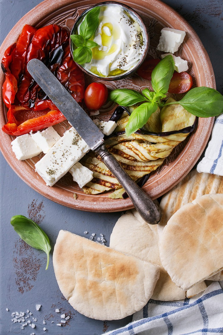 Ingredients for making pita bread sandwiches. Grilled vegetables, basil and feta cheese with flat bread on terracotta plate over gray texture backgrou