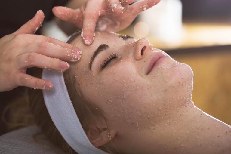 Beautician applying exfoliating salt scrub on woman's face