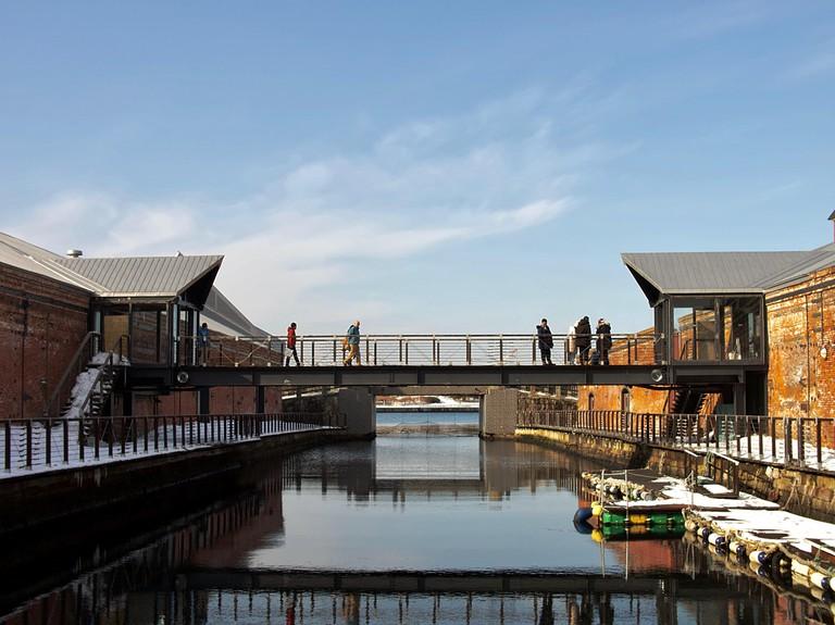 Visitors crossing bridge linking 2 warehouses at Hakodate's Red Brick Warehouse area, Hokkaido, Japan