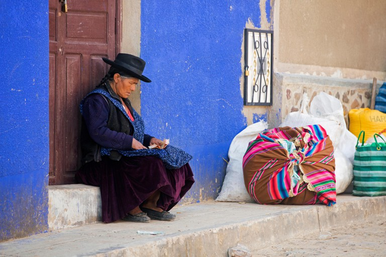Woman counting money in traditional cholita dress in the town of Tarabuco