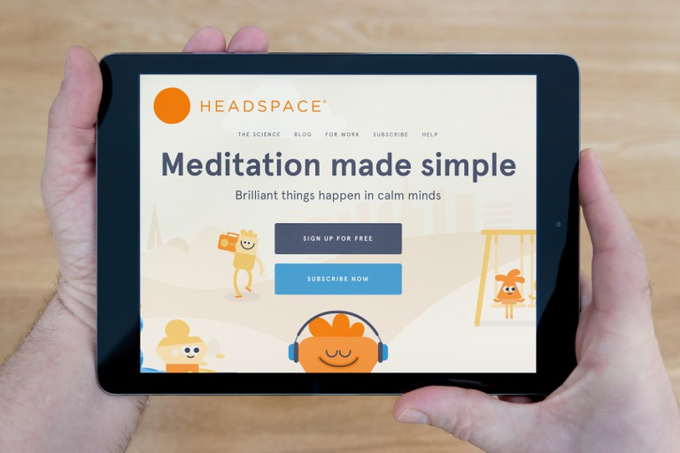 A man looks at the Headspace meditation website on his iPad tablet device, shot against a wooden table top background (Editorial use only)