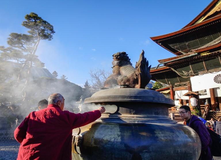 People praying at Zenkoji Temple in Nagano, Japan.