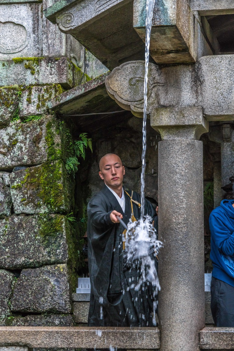 Local Monk drinking water from Otowa Waterfall (Otowa-no-Taki) which is believed to have wish-granting powers. Kiyomizu-dera Temple in Kyoto, Japan