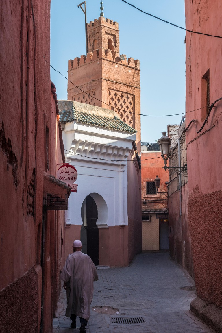 Back street in the medina with traditional architecture, windows, doors and arches and Mosque.