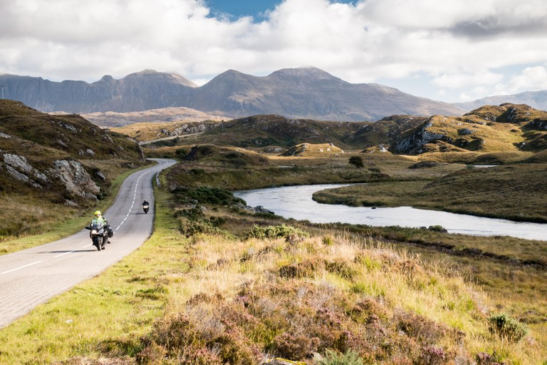 The A837 road, part of the North Coast 500 route, meanders past rivers and low hills in the glacial landscape of Assynt, with Quinag mountain in the d