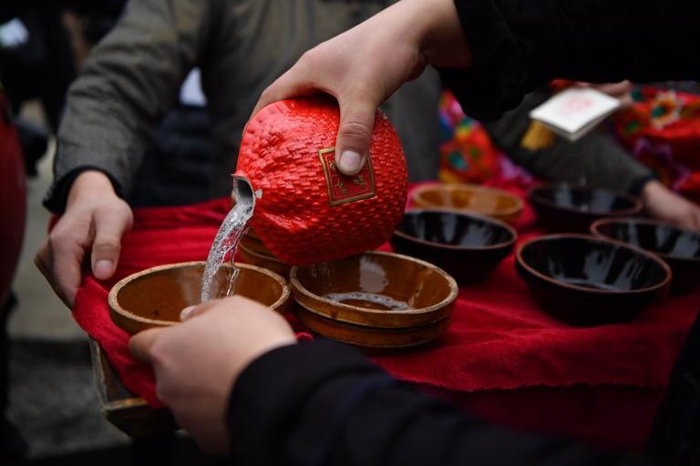 A man pours Chinese spirit baijiu to bowls