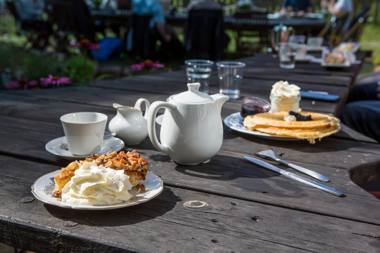 A table outdoors with coffee, cakes and a can of milk. A typical swedish fika in the sunshine.
