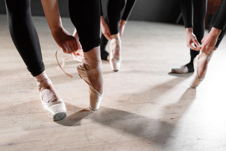 The ballet concept. Pointe shoes close up. Young ballerina girls. Women at the rehearsal in black bodysuits. Prepare a theatrical performance