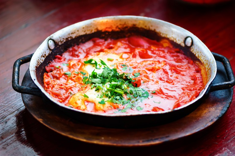 Shakshuka. Traditional jewish food and middle eastern cuisine recipe. Fried eggs, tomatoes, bell pepper and parsley in a pan. Close up, selective focu