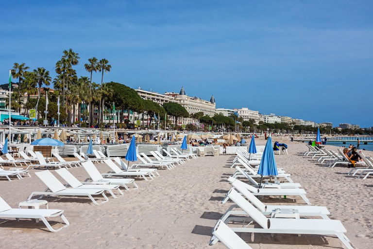 France, Cannes city, beach with sun loungers on French Riviera at Mediterranean Sea, buildings along Boulevard de la Croisette