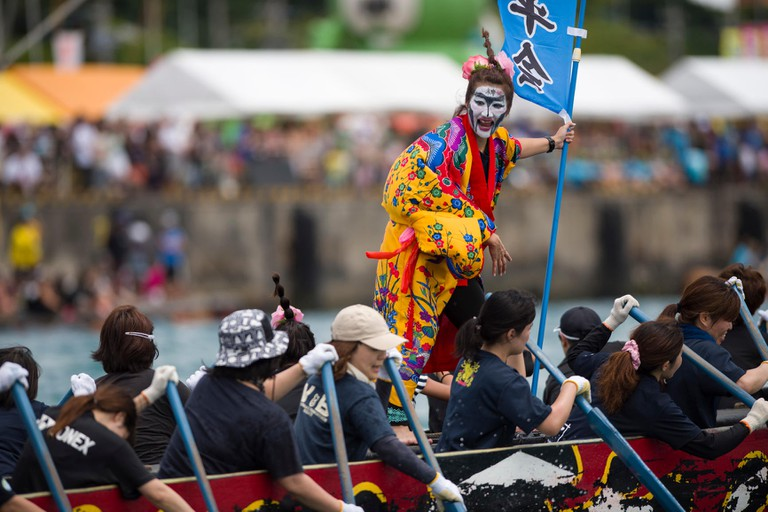 A dragon boat team member dressed in Ryuku traditional garb cheers on her teammates during the Naha Dragon Boat Race May 5, 2017, at Naha Port