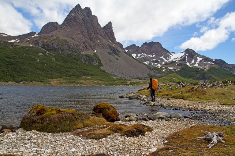Hiker on the shores of Laguna Martillo along the Dientes Circuit