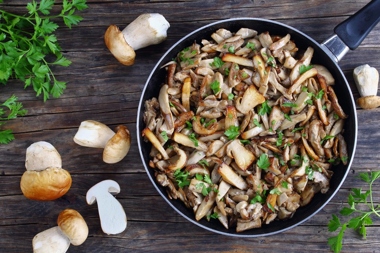 delicious Side dish - Funghi trifolati or fried Boletus porcini mushrooms sprinkled with finely chopped parsley in skillet on old dark wooden table wi