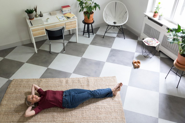 Relaxed mature woman lying on the floor at home