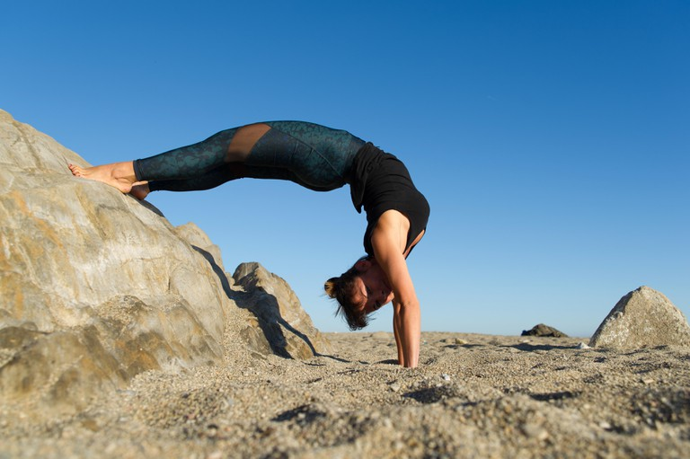 Argeles-sur-Mer (south-eastern France). Stretching exercises after practising yoga on the rocks in front of the Racou Beach in the early morning